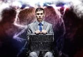 Young businessman under rain sitting on chain