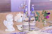 Decoration For Wedding Table In Purple Color . Bottle Of Champagne, Flowers And Candles.