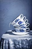 Stack of pretty blue and white vintage teacups with spilling milk