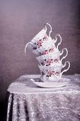 Stack of antique cups with splashed milk - vintage tone filter effect added