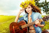 stock photo of hippies  - Romantic girl in a wreath of wild flowers playing her guitar - JPG