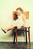 Sweet little girl in a beautiful white dress sitting on the old chair by the white brick wall. Child