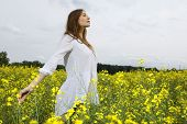 Beautiful and sensuality young adult brunette woman in a yellow flowers field in outdoor