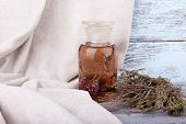 Bottles of herbal tincture and dried herbs on a napkin on wooden background in front of curtain
