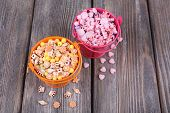 Beads in metal buckets on wooden background
