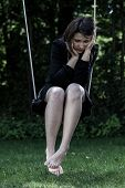 Picture of worried woman sitting on swing.