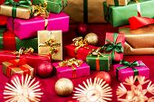 stock photo of gift wrapped  - Many Christmas presents placed on a red cloth among baubles and stars - JPG