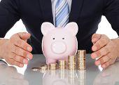 Businessman Sheltering Coins And Piggybank At Desk