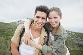 Portrait of hiking young couple standing on mountain terrainPortrait of hiking young couple standing