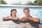 Portrait of a smiling young couple in swimming pool on a sunny day