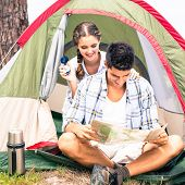 Smiling young couple looking at map outside their tent