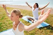fitness, sport, friendship and lifestyle concept - smiling couple making yoga exercises sitting on m