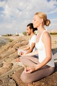 fitness, sport, friendship and lifestyle concept - smiling couple making yoga exercises sitting outd