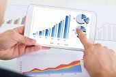 Businessman Comparing Graphs On Digital Tablet At Office Desk