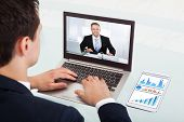 foto of video chat  - Cropped image of young businessman video conferencing on laptop at desk in office - JPG