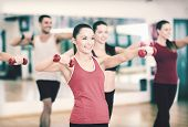 fitness, sport, training, gym and lifestyle concept - group of smiling people working out with dumbb