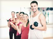 fitness, sport, training, gym and lifestyle concept - group of smiling people lifting dumbbells in t