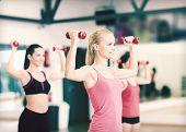 fitness, sport, training, gym and lifestyle concept - group of smiling women working out with dumbbe