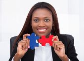 Confident Businesswoman Holding Puzzle Pieces In Office