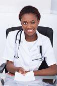 Female Doctor Giving Prescription Paper At Desk