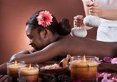 African American Woman Enjoying Herbal Massage At Spa Salon