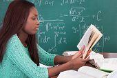 Teacher Reading Book At Classroom