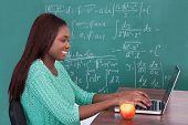 Teacher Using Laptop At Classroom