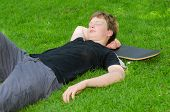 Teenager With Skate Resting On Grass