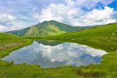 Mountain lake with clouds reflection in water