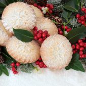 Christmas mince pie cakes with holly, ivy, mistletoe and snow covered fir.