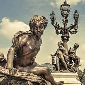 detail of the richly ornamented Alexandre III Bridge in Paris, France, with a retro effect
