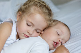 image of matron  - charming little brother and sister asleep embracing on white background - JPG