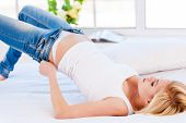 foto of pulling hair  - Young blond hair woman lying on the bed and pulling on tight jeans - JPG