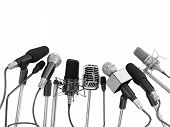 Various Microphones Aligned At Press Conference Isolated Over A White Background.