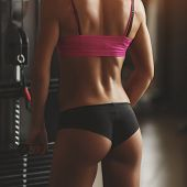 picture of fitness-girl  - Brutal athletic woman pumping up muscles with dumbbells - JPG
