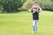 Asian Family Concept - Father Giving Daughter Piggyback Ride