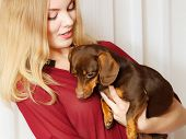 foto of petting  - Pets and people pet adoption. Elegant woman posing with her mixed dog pet indoor hugging lovingly embraces her puppy.