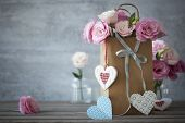 Love's still life background with pink roses, ribbons and handcrafted hearts