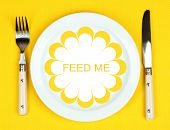 Plate with text Feed Me, fork and knife on tablecloth background