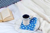 Book and cup of tea on bed close-up