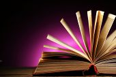 Open book over dark colorful background