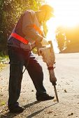 stock photo of hammer drill  - worker with pneumatic hammer drill equipment ready to breaking asphalt at road - JPG