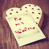a heart-shaped biscuit and a instant photo with the text be my valentine on a wooden table, with a retro effect