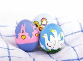 picture of duck egg blue  - Bright colored hand painted Easter eggs with cute animals on a soft white and blue towel - JPG