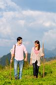 Постер, плакат: couple of man and woman hiking on mountain summit or alpine grassland in the Bavarian Alps enjoys t