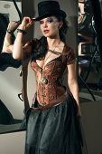 stock photo of bosoms  - Girl with vintage gun in steampunk style standing near the mirror - JPG