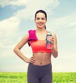 sport, exercise and healthcare - sporty woman with pink towel and water bottle