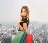 people, holidays and sale concept - young happy woman with shopping bags over city background