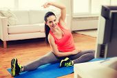 fitness, home and diet concept - smiling teenage girl stretching on floor and watching tv at home