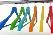 Row of color coat hangers on metal clothes rail. 3d illustration on white background